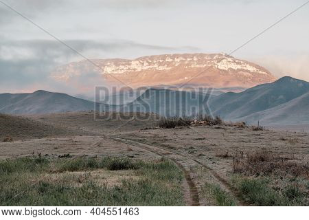 Dirt Road In Field Going Into Mountains. Dawn In Autumn Field. Hills In Morning Haze. Grass Covered