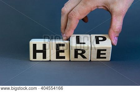 Help Is Here Symbol. Businessman Turns Cubes And Changes The Word Help To Here. Beautiful Grey Backg