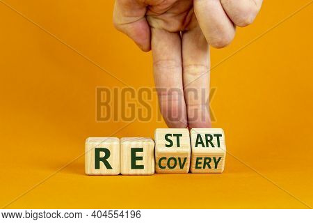 Recovery And Restart Symbol. Businessman Hand Turns Cubes And Changes The Word 'recovery' To 'restar