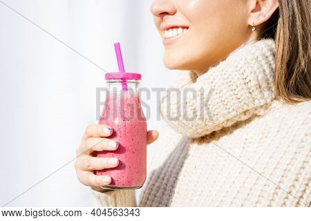 Happy Smiling Woman In Woollen Sweater Holding Bottle With Pink Homemade Strawberry Or Cherry Milksh