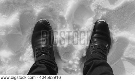 Man's Feet In The Snow, Black Boots In The Snow Top View, A Man Standing In The Snow-white Snow