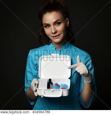 Young Smiling Woman Doctor Nurse In Blue Uniform And Protective Latex Gloves Holding First Aid Kit I
