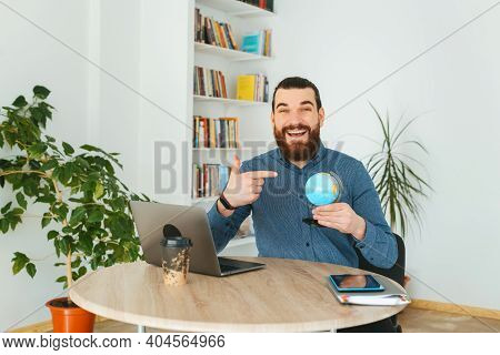 Photo Of Cheerful Bearded Man In Office Pointing At Globe