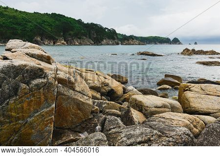 Cloudy Summer Day On The Sea With A Rocky Shore Coastline Of The Bay.