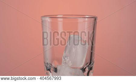 Close Up Of Ice Cubes Falling Into A Cocktail Empty Glass Isolated On Pink Background. Action. Makin
