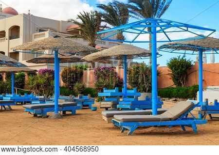 Sun Umbrellas And Chaise Lounges On Tropical Beach. Concept Of Rest, Relaxation, Holidays, Resort