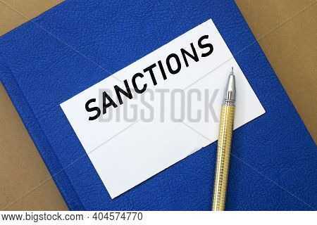 On A Blue Notebook With A White Sheet The Word Sanctions Is Written. Political And Economic Concept