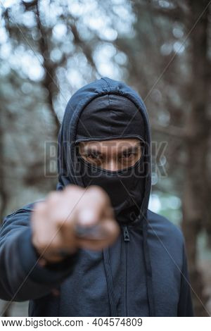 Masked Man With A Knife Wearing Black Clothes With Menacing Eyes