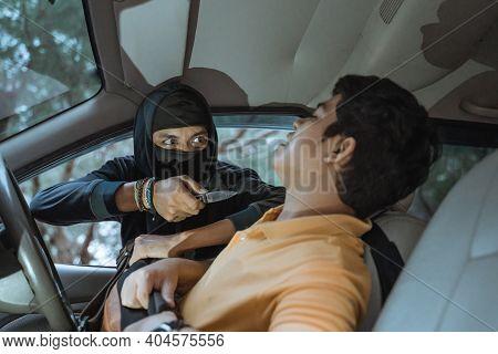 Close Up Of Man Wearing Mask Using Knife Threatening Car Driver