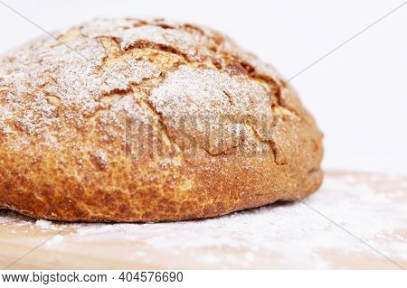 Round Bread With A Crispy Crust On A Wooden Board. Close-up.