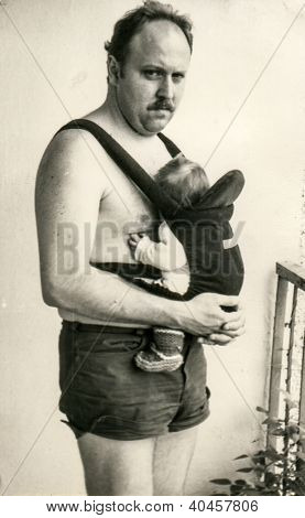 Vintage photo of father with baby daughter in baby carrier (1981)