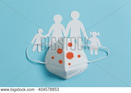 Silhouette Of Family Cut From Paper Covered With Medical Face Mask N95 Top View On Blue Background.