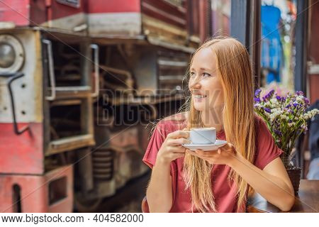 Young Woman Traveler Drinks Vietnamese Coffee With Egg Sitting By The Railway Paths Which Go Through