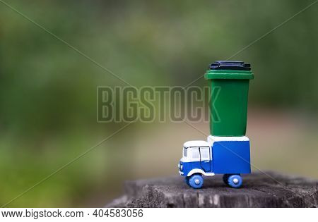Toy Garbage Truck With A Green Garbage Can Standing On A Tree Hemp Against A Blurred Forest Backgrou