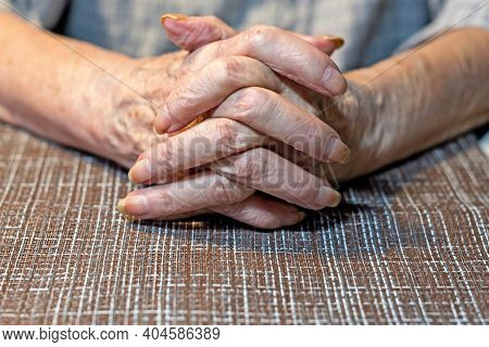The Hands Of An Elderly Woman Resting On The Table. Parkinson