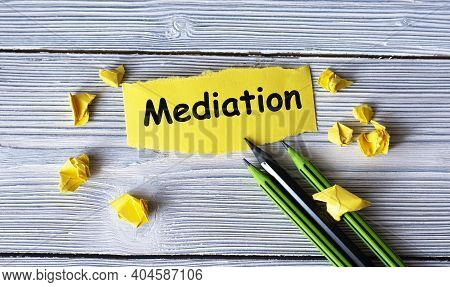 Mediation - Word On A Yellow Tattered Piece Of Paper With Pencils And Crumpled Paper Lumps On A Ligh