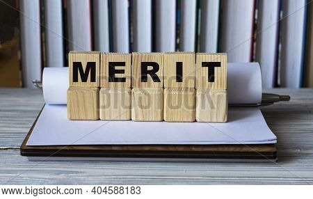 Merit - Word On Wooden Cubes In A Notebook On The Background Of Books.