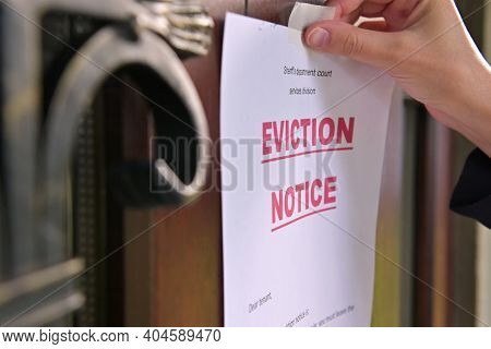 Close-up Of A Tenants Eviction Notice Gluing To The Door