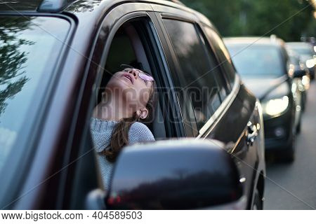 A Young Woman Stands In A Traffic Jam And Looks Out Through The Window Trying To Discern The Cause O