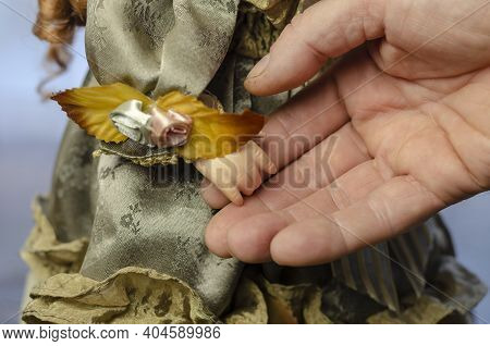 A Man's Hand Touches The Hand Of A Child's Doll. Doll's Dress With Flowers And Lace In Vintage Style