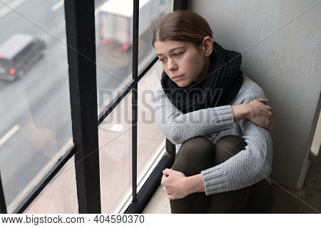 A Sad Young Woman, A Resident Of The City, Leaned Her Head Against The Window And Looks With Sadness