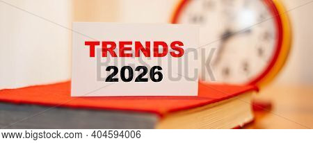 Trends Of 2026 On An Orange Background. Future Trends Against The Background Of Clocks