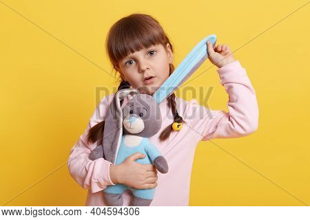 Adorable Little Girl With Toy Rabbit Isolated Over Yellow Background, Child Pulling Bunny's Ear And