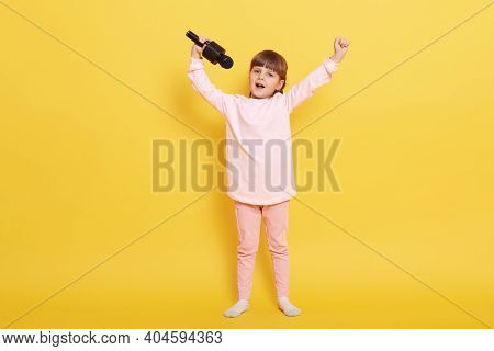 Small Girl With Microphone Singing Against Yellow Color Background, Keeping Hands Up, Arranges Conce
