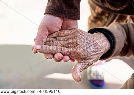 Hands Of Senior Woman And Young Adult Woman Caring For The Elderly. Close-up Of Carer Hand Holding T
