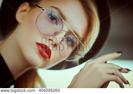 Optics, eyewear. Close-up portrait of a fashionable young woman in modern glasses and a hat in interiors. Beauty, fashion concept.