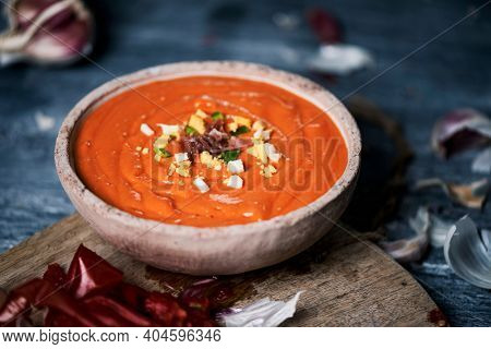closeup of an earthenware bowl with freshly made spanish salmorejo cordobes or porra antequerana, a cold tomato soup topped with serrano ham, boiled egg and green pepper, on a gray table