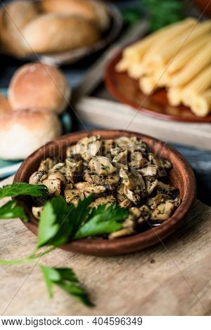 closeup of some sliced mushrooms cooked with garlic and parsley served in an earthenware plate, on a gray wooden table next to some plates with some cooked baby corns and some buns in the background