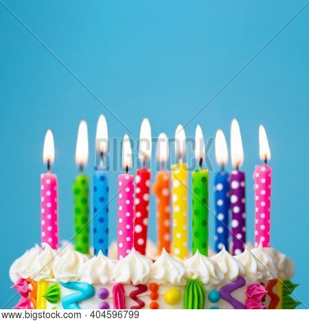 Colorful birthday cake with rainbow colored candles