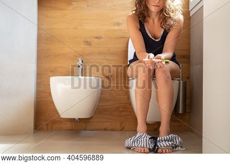 Worried woman sitting on pot holding pregnancy test stick and wait for the result. Tensed young woman looking at pregnancy stick in bathroom with copy space. Anxious teenager holding a pregnancy test.
