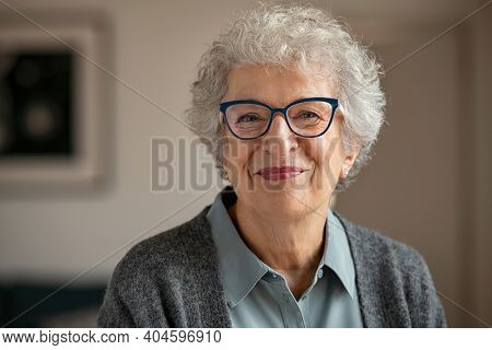 Portrait of happy retired senior woman looking at camera while wearing new eyeglasses. Smiling satisfied old woman at home. Closeup face of wrinkled beautiful grandmother trying on new eyewear.