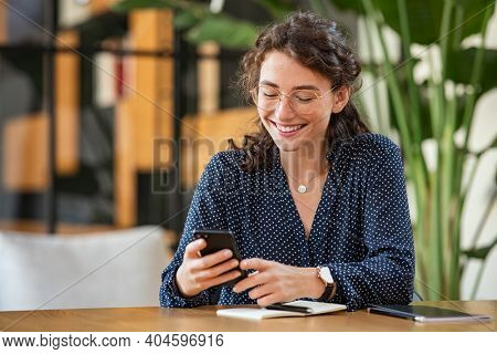 Young smiling business woman sending text message with smartphone at desk. Woman using mobile phone to check email at work with copy space. Cheerful student girl messaging online with cellphone.