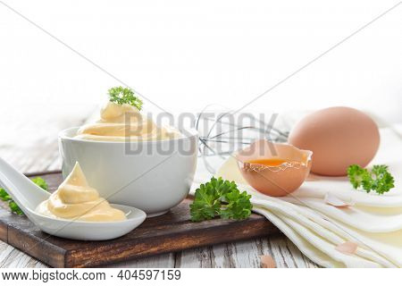 Bowl of Mayonnaise sauce on white wooden table, close-up