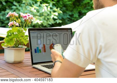 Man works on laptop in the garden and drink coffee. Home office with relax and nature. Freelancer outdoors.