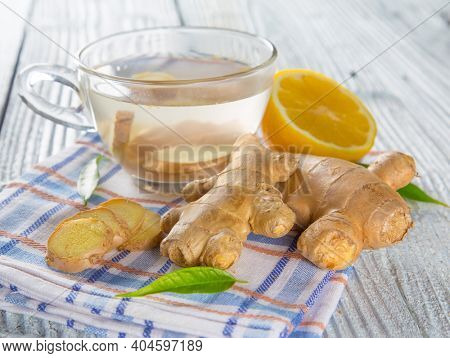 Lemon and ginger root with tea on wooden background, close-up.
