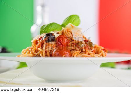 Pasta with meat, tomato sauce, parmesan and vegetables, close-up