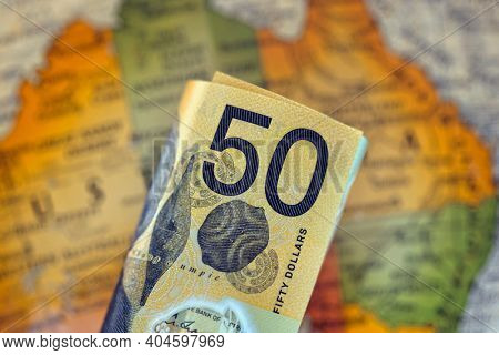 Australian fifty dollar note over blurred map of Australia.  Finance background.