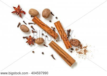 Cinnamon sticks, nutmeg, star anise, cloves and peppercorns isolated over white.  Top view, flat lay.  Traditional Christmas spices.