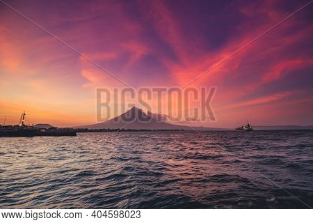 Philippine ocean sunrise silhouette, Volcano Mayon erupt cloud haze. Tropic Asia seascape of water transport: ships, boats at harbor. Picturesque sea bay and coast with small cottage, lodge, building