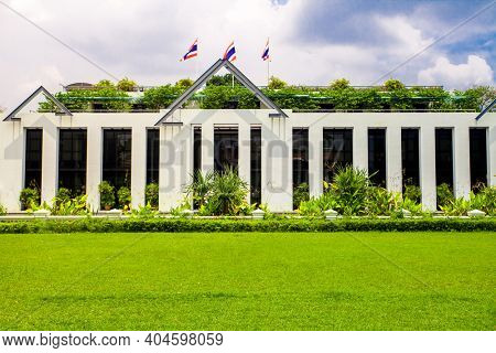 Asia botanic garden building exterior and green grass lawn with plant and flags on roof top. Modern Thailand greenery designed landscaping house in soft light shot. Exotic Thai tropical botany flora