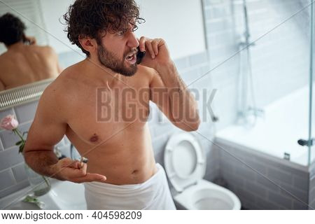 Dissatisfied topless man fighting while brushing teeth in the bathroom