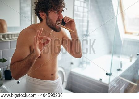Dissatisfied topless man fighting while brushing teeth in the morning