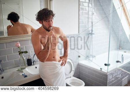 Handsome topless man brushing teeth in the morning