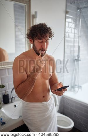 Topless man texting while brushing teeth in the morning