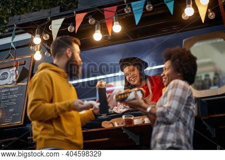 female employee socializing with multiethnic couple eating sandwiches in front of fast food service, laughing, talking, smiling