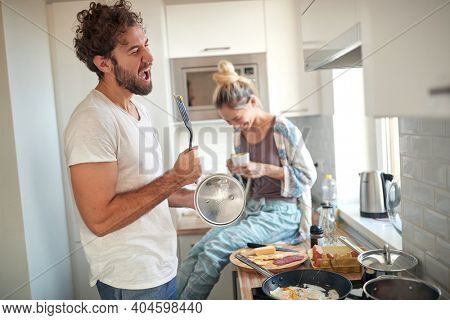 Happy couple making breakfast together in the kitchen